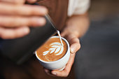 Coffee Art In Cup. Closeup Of Barista Hands Making Latte Art  Picture With Milk On Coffee. High Resolution
