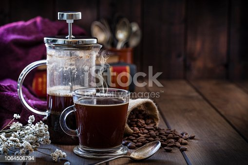 Front view of a transparent glass coffee cup and a coffee french press placed at the left of a rustic wooden table leaving useful copy space for text and/or logo at the center-right. A burlap sack with roasted coffee beans and old books at background complete the composition. Predominant color is brown. Low key DSRL studio photo taken with Canon EOS 5D Mk II and Canon EF 100mm f/2.8L Macro IS USM.