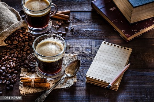 High angle view of two transparent coffee cups placed at the left of a rustic wooden table A blank note pad is beside the coffee cup with useful copy space for text. A burlap sack with roasted coffee beans complete the composition. Predominant color is brown. Low key DSRL studio photo taken with Canon EOS 5D Mk II and Canon EF 100mm f/2.8L Macro IS USM.