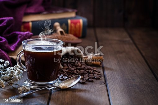 High angle view of a transparent glass coffee cup placed at the left of a rustic wooden table leaving useful copy space for text and/or logo at the center-right. An old metal spoon is in front of the coffee cup. Roasted coffee beans are behind the cup. Two old books are out of focus at background and complete the composition. Predominant color is brown. Low key DSRL studio photo taken with Canon EOS 5D Mk II and Canon EF 100mm f/2.8L Macro IS USM.