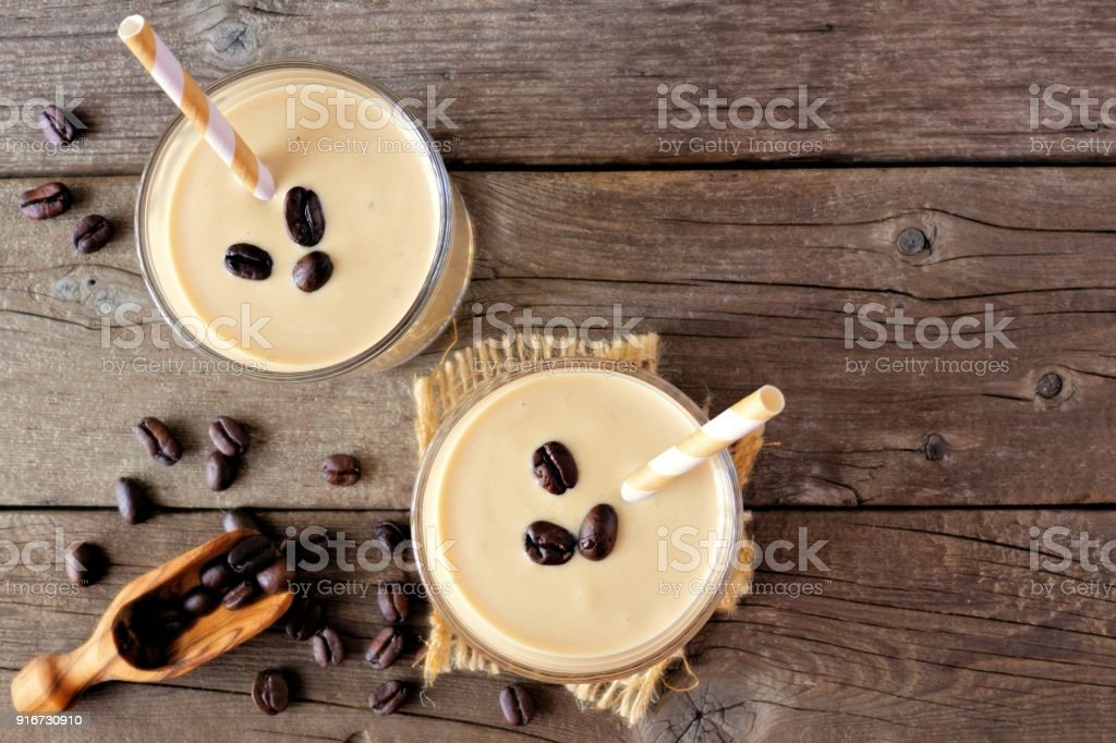 Coffee, banana smoothie in glasses, top view over wood stock photo