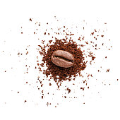 Extreme close up view of a single roasted coffee bean placed on top of a small heap of ground coffee shot from above on white background. Predominant colors are brown and white. High key DSRL studio photo taken with Canon EOS 5D Mk II and Canon EF 100mm f/2.8L Macro IS USM.