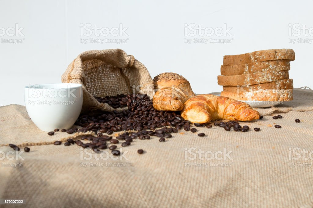 Coffee bean in burlap bag with coffee cup, sliced bread and croissant stock photo