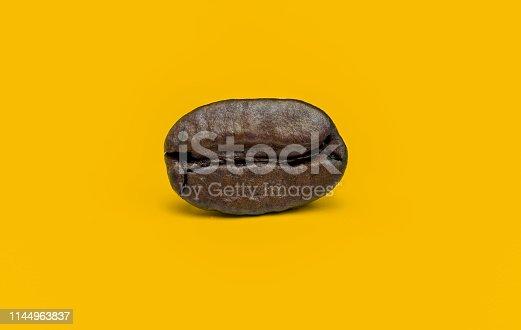 Single dark roast coffee bean on yellow background.