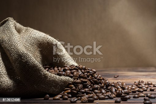 istock Coffee beans and bag on old rusty background 812612498