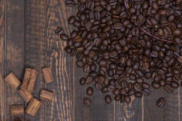 Kaffeebohnen und Zimt auf einer Holzfläche – Foto