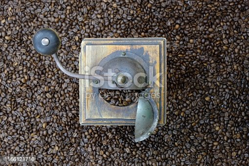 Vintage coffee grinder on a coffee bean background. View from above flat lay.