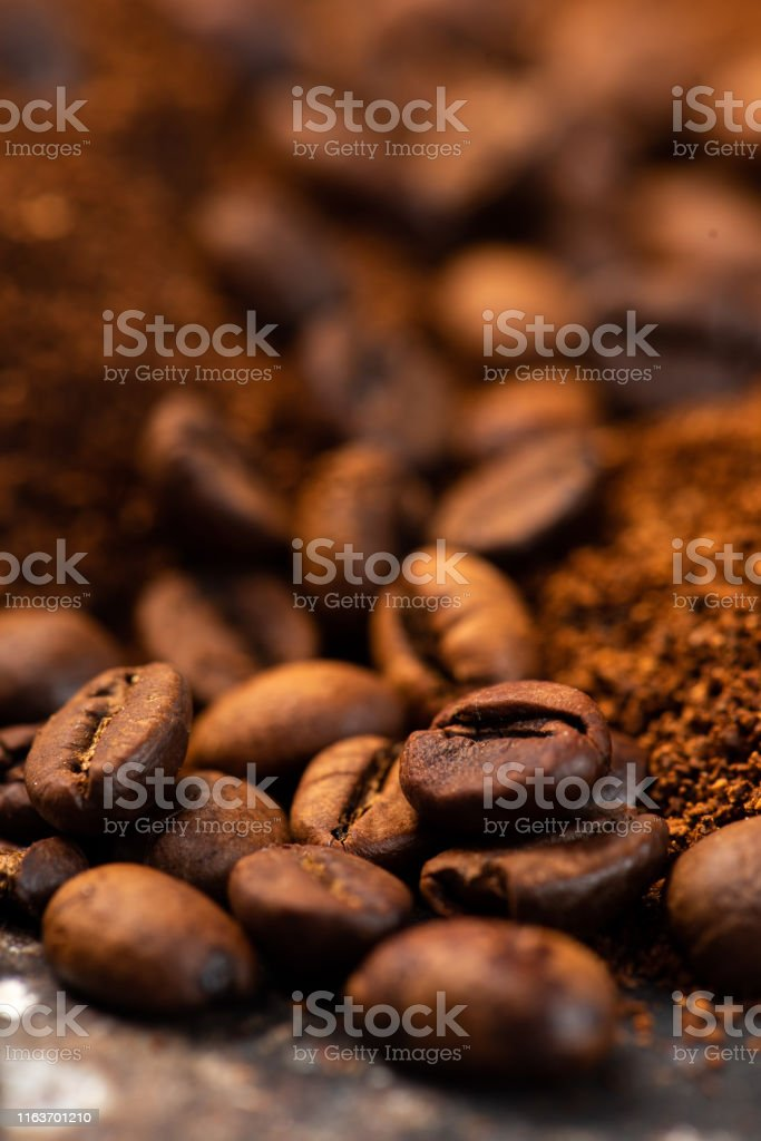 Coffee beans and ground coffee background Some coffee beans over ground coffee for coffee theme backgrounds Above Stock Photo