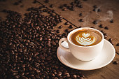 istock Coffee beans and Hot Cofee cup with latte art on wooden background. side view with copy space for your text 814684194