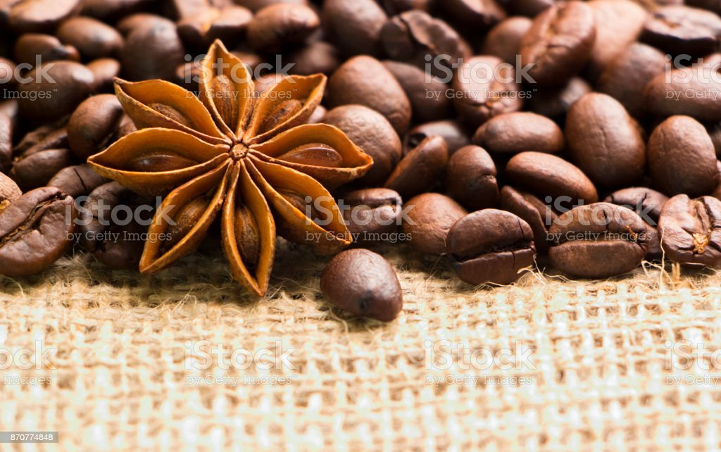 coffee beans and star anise on coarse fabric stock photo