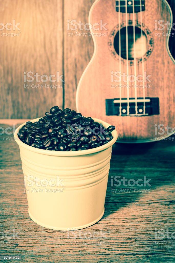 Coffee beans and Ukulele on wood background stock photo