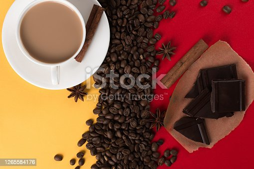 istock Coffee beans are scattered on a red and yellow paper background and a white cup, cinnamon, star anise, chocolate, concept, commercial copy space. 1265584176