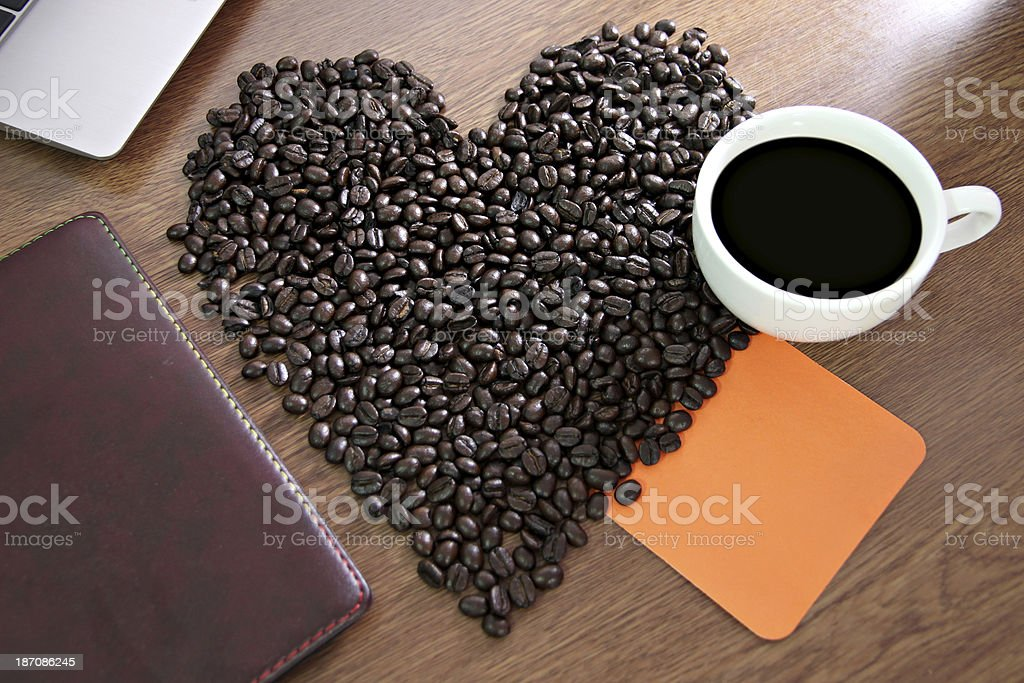 Coffee beans arranged a heart shape and placed paper Notebook. royalty-free stock photo