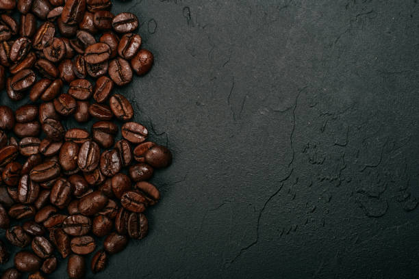 Coffee beans background Roasted brown coffee beans on the black concrete stone background. Flatlay style, messy pattern. black coffee stock pictures, royalty-free photos & images