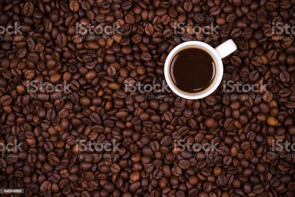 Coffee beans background with white cup stock photo