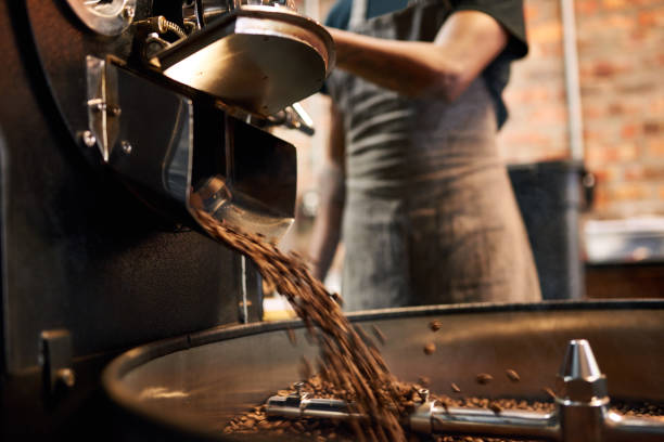 coffee beans being poured out of a coffee roasting machine African man wearing an apron busy pouring coffee beans from the coffee roasting machine over to the tray that stirs the beans until they are cool enough to be packaged. barista stock pictures, royalty-free photos & images