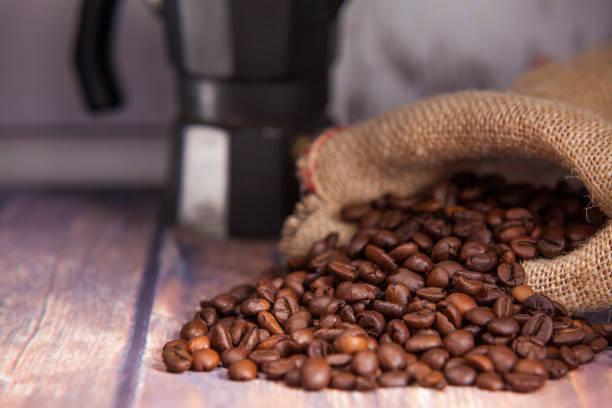 granos de café que salen de un saco y cafetera - foto de stock