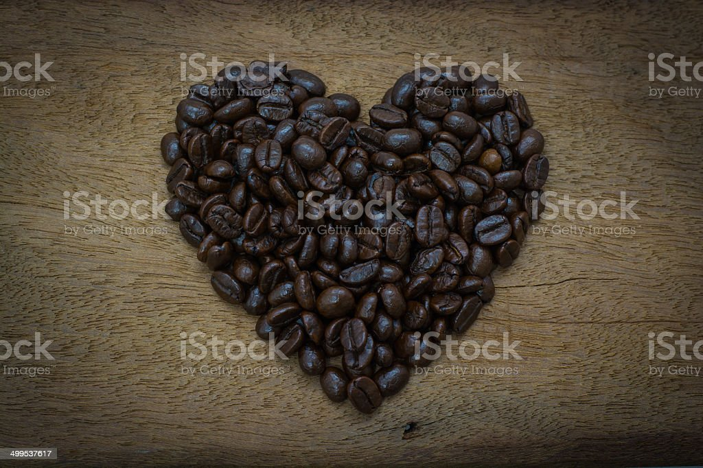 Coffee beans heart shape on wood royalty-free stock photo