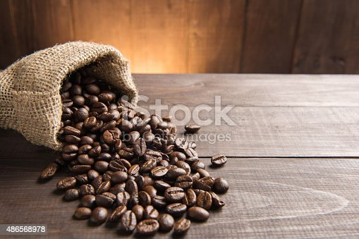 istock coffee beans in a bag on wooden background. 486568978