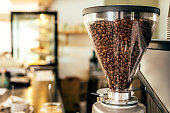Coffee beans in a big glass grinder machine holder with blurred background of a cafe.