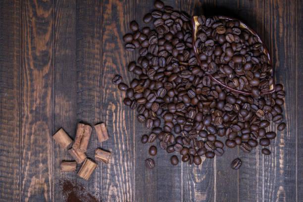 Kaffeebohnen in einer Tasse und Zimt auf einem Holztisch – Foto