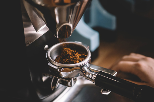 Coffee beans in a portafilter by the coffee grinder