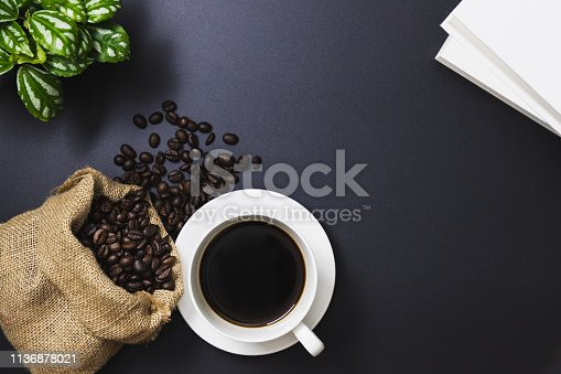 istock Coffee beans in a sack bag and black coffee in a white coffee mug, trees, books 1136878021