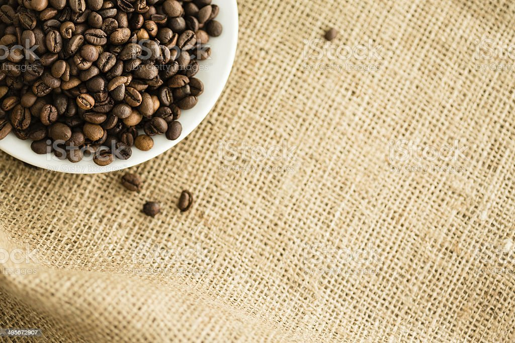 Coffee beans in a saucer on burlap stock photo
