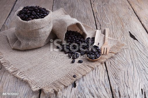 istock Coffee beans in bag with wooden spoon on old wood plank. 887920532