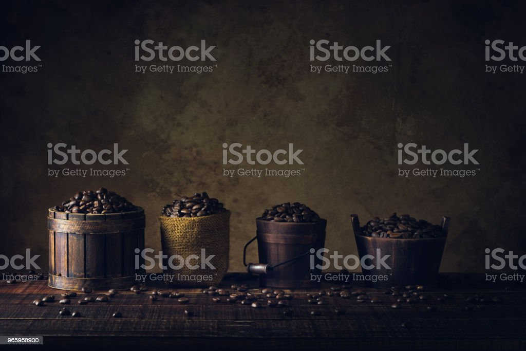 coffee beans in container on wood floor and old paper vintage aged background or texture - Royalty-free Backgrounds Stock Photo