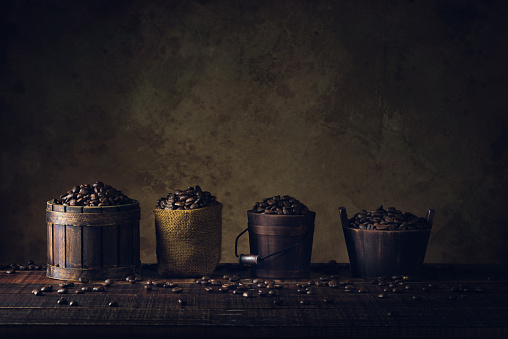 Coffee Beans In Container On Wood Floor And Old Paper Vintage Aged Background Or Texture Stock Photo - Download Image Now