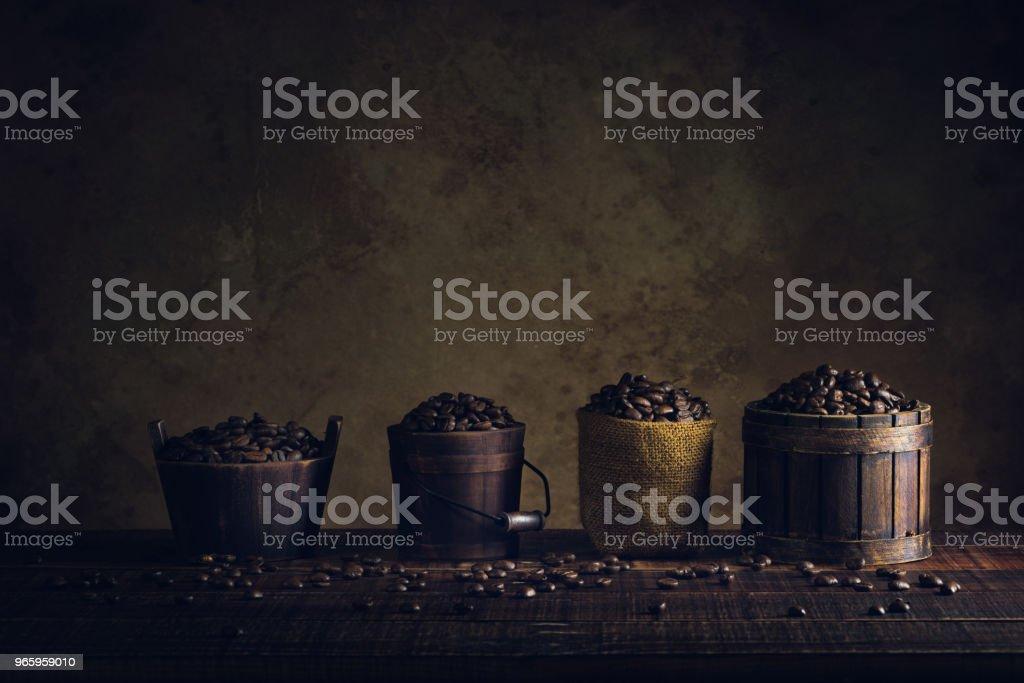 koffiebonen in de container op de houten vloer en oud papier vintage leeftijd, achtergrond of textuur - Royalty-free Achtergrond - Thema Stockfoto
