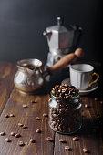 Coffee beans in glass jar on dark wooden background with cezve, geyser coffee maker