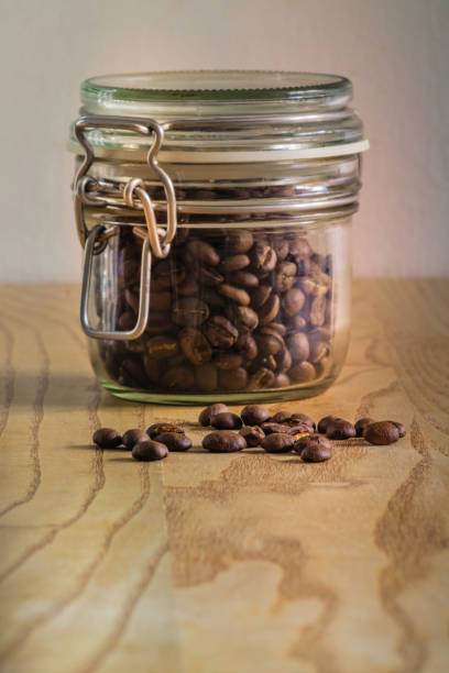 Coffee beans in jar and on table stock photo