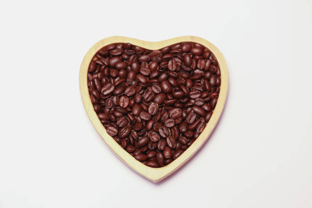 coffee beans in the heart shape wooden plate stock photo