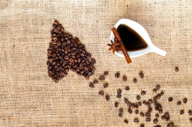 咖啡豆的形狀在心臟和老式白色陶瓷杯咖啡, 肉桂棒, 八角明星在黃麻袋。複製空間。閉上你的嘴平躺著。 - 咖啡 飲品 個照片及圖片檔