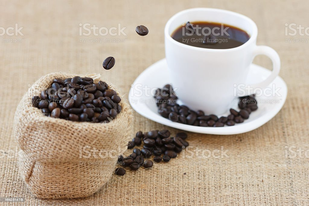Coffee beans jumping into white cup royalty-free stock photo
