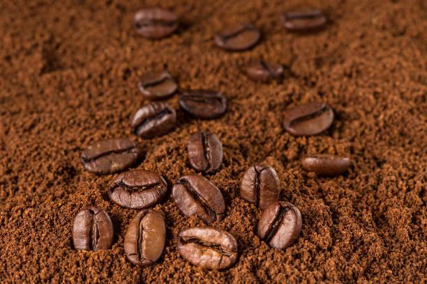 kaffeebohnen-makro auf gemahlenen kaffee hintergrund. - kaffeepulver stock-fotos und bilder