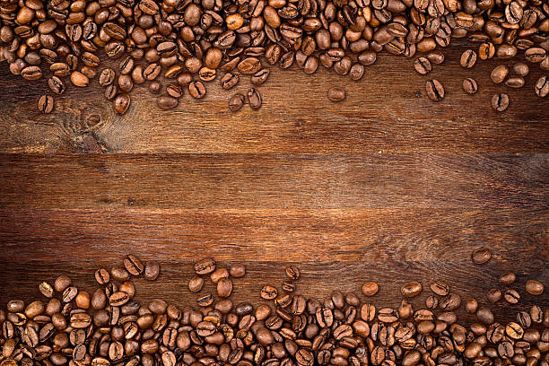 coffee beans old oak background - coffee beans stock photos and pictures