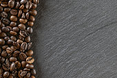 Coffee beans on black caffeine breakfast background. For cup of dark espresso food or drink. Assorted ground and instant brown roasted coffee seeds on stone. Copy space, top view.