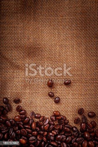 istock Coffee beans on burlpab background 185232662