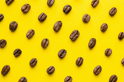 Coffee beans pattern isolated on yellow background. Top view