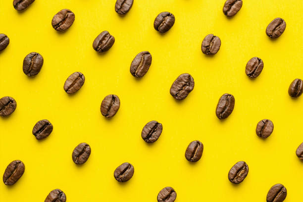 Coffee beans pattern on yellow background Coffee beans pattern isolated on yellow background. Top view roasted coffee bean stock pictures, royalty-free photos & images