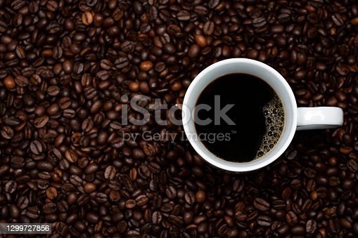 This image shows beautiful brown coffee beans with a cup of coffee.