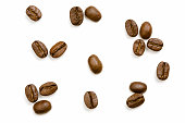 Direct above view of roasted coffee beans, coffee types in spoons,  coffee cup with coffee and coffee maker on wooden background.
