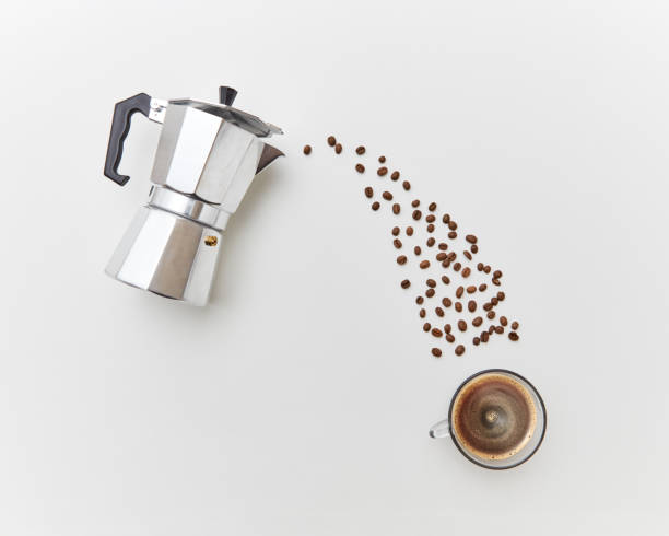 Coffee beans pour in a cap with drink from a metal coffee maker on a white background. Flat lay stock photo