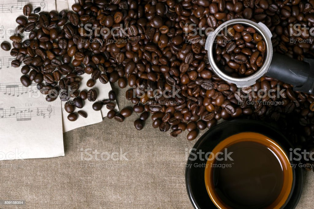 Coffee beans, sheet music and Coffee cup on a burlap background stock photo