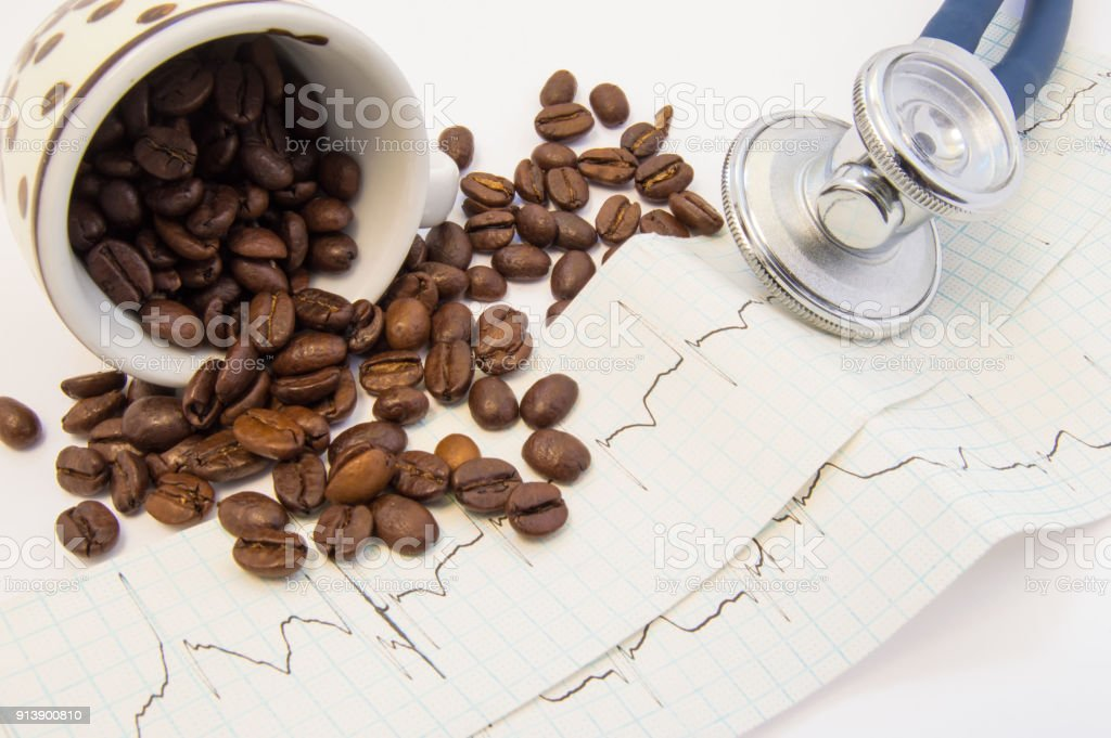 Coffee beans spilled from c and scattered on paper ECG near medical stethoscope. Effect of coffee and caffeine on cardiovascular system, heart rate, function and activity, pulse and blood vessels stock photo
