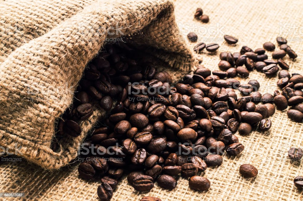 Coffee beans spilled from the bag. Horizontal stock photo