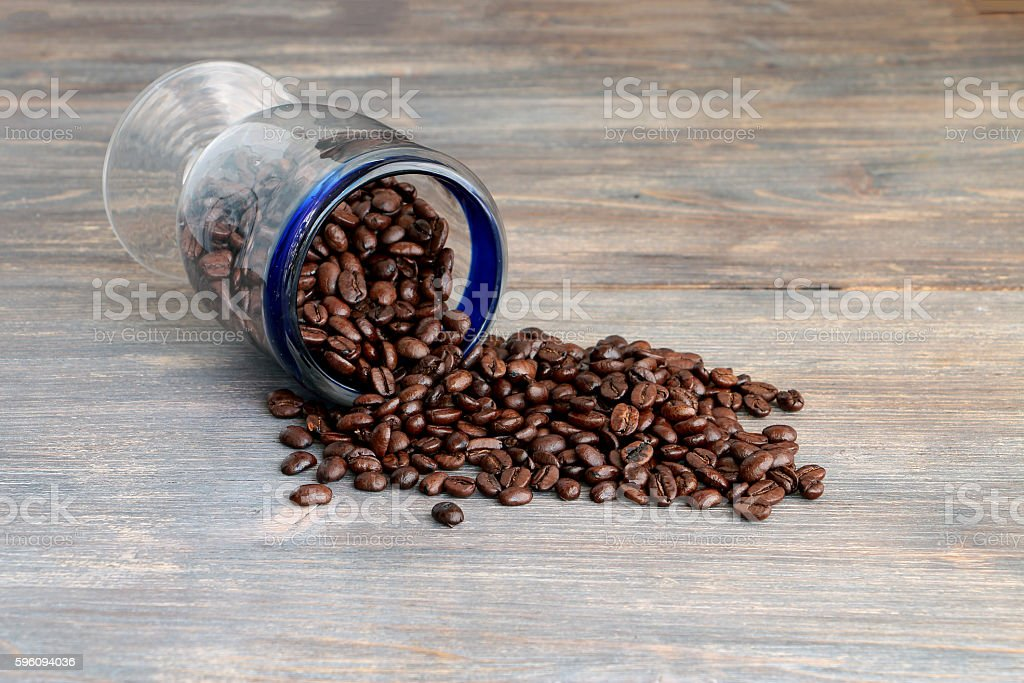 Coffee beans spilled on a wooden table. royalty-free stock photo